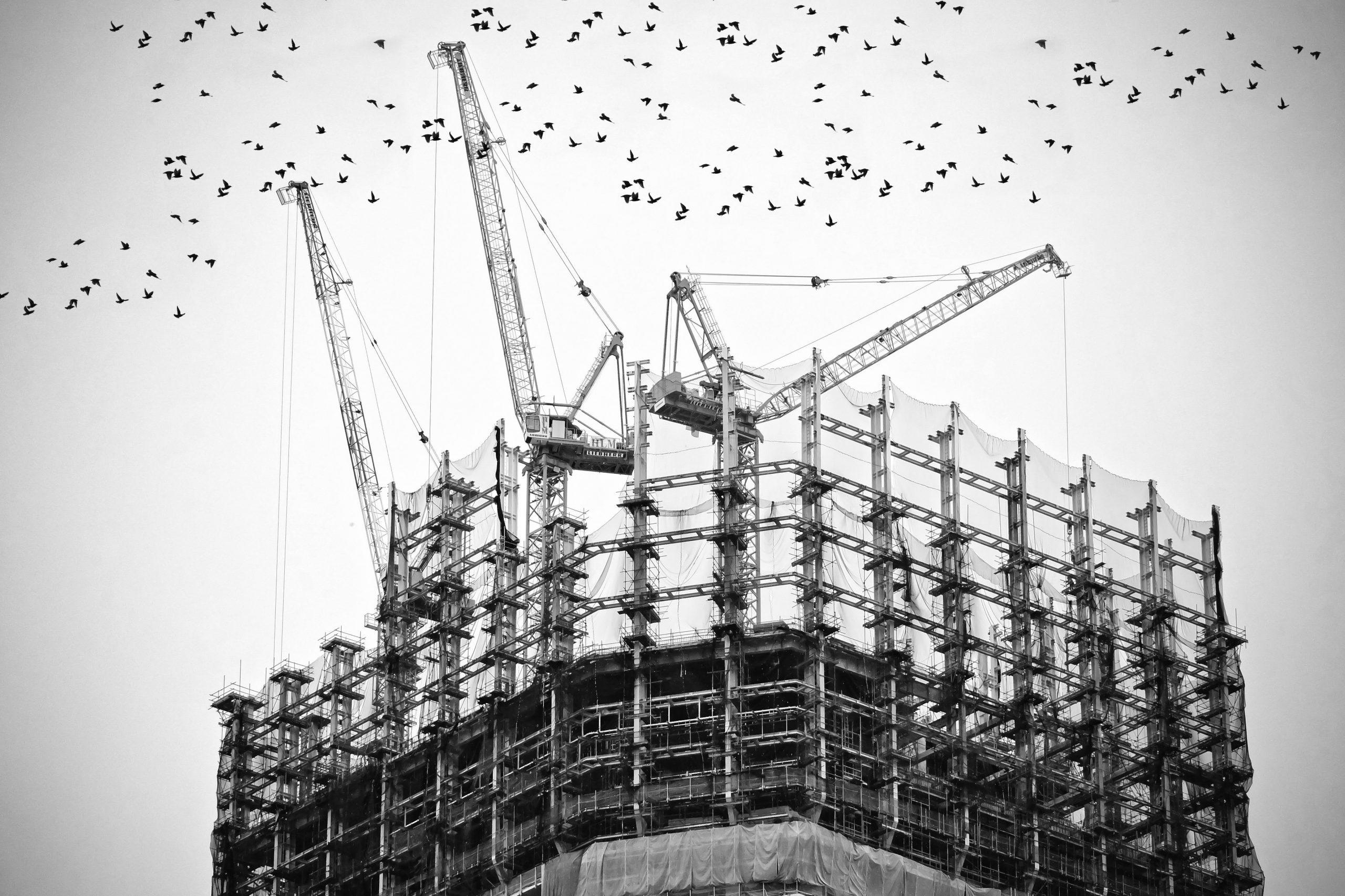Un immeuble en construction avec trois grues